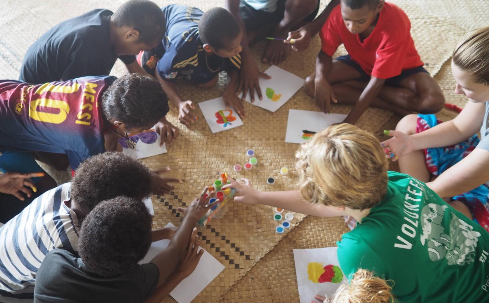 Projects Abroad vrijwilligers spelen een balspel met kinderen in een kleuterschool in plaats van te werken in een weeshuis in het buitenland.